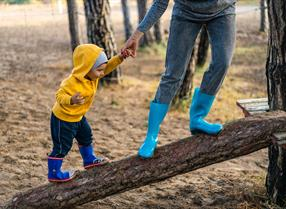 Parent and child wearing welly boots balancing on a log in woodland