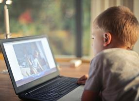 Young boy watching film of children on laptop