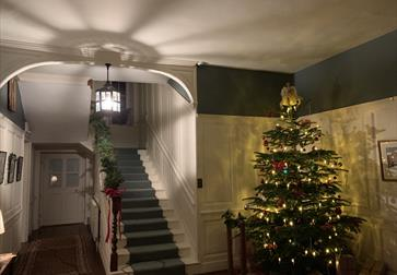 The hallway and staircase at Lamb House with Christmas tree